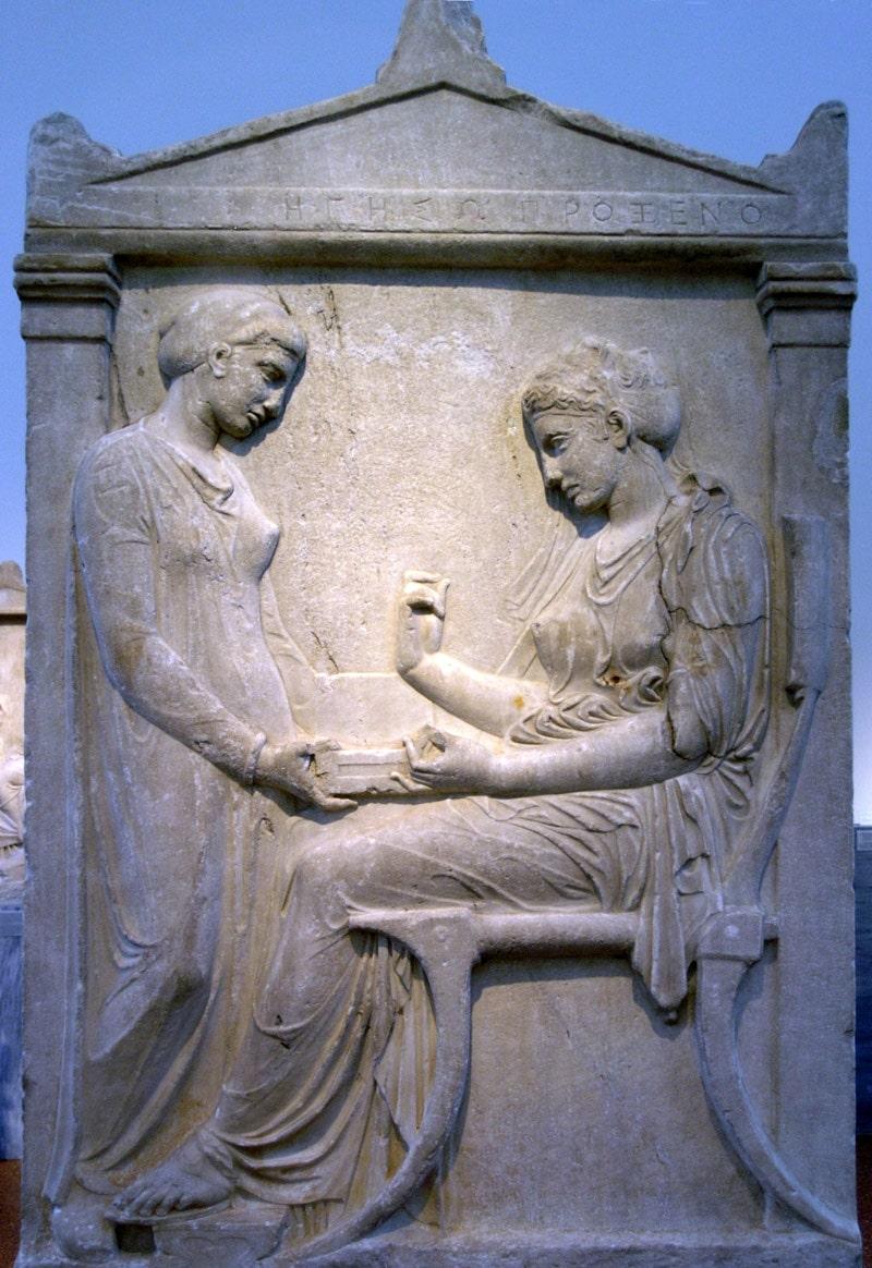 Stèle funéraire de marbre pentélique trouvée à l'Ouest d'Athènes dans le Céramique. Une Athénienne est assise sur une chaise avec un repose pieds et regarde un bijou tenu de la main droite et peint à l'origine. En face d'elle se tient une esclave tenant une boîte à bijoux ouverte. D'après l'inscription sur l'épistyle, la défunte est Hegeso, fille de Proxenos : la qualité du travail indique une famille noble, et l'œuvre a été attribuée au sculpteur Callimaque. Fin du Ve s. av. J.-C.